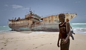 A masked pirate stands by a washed up Taiwanese fishing vessel in the once-bustling pirate den of Hobyo, Somalia. The crew were released after a ransom was paid. Photograph: Farah Abdi Warsameh/AP