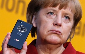 Merkel holds her mobile used for governmental communication during her opening tour at the CeBit computer fair in Hanover (REUTERS/Fabrizio Bensch)