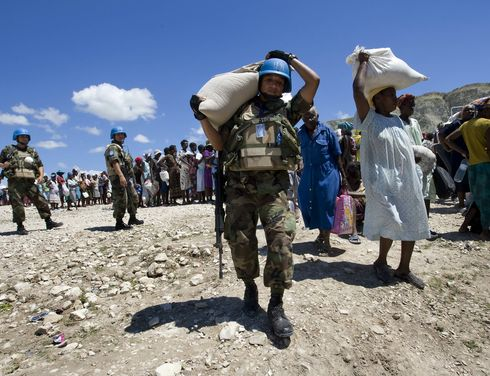 A United Nations soldier, part of the multinational peacekeeping mission in Haiti, helps a local woman carry donated food from a distribution center.