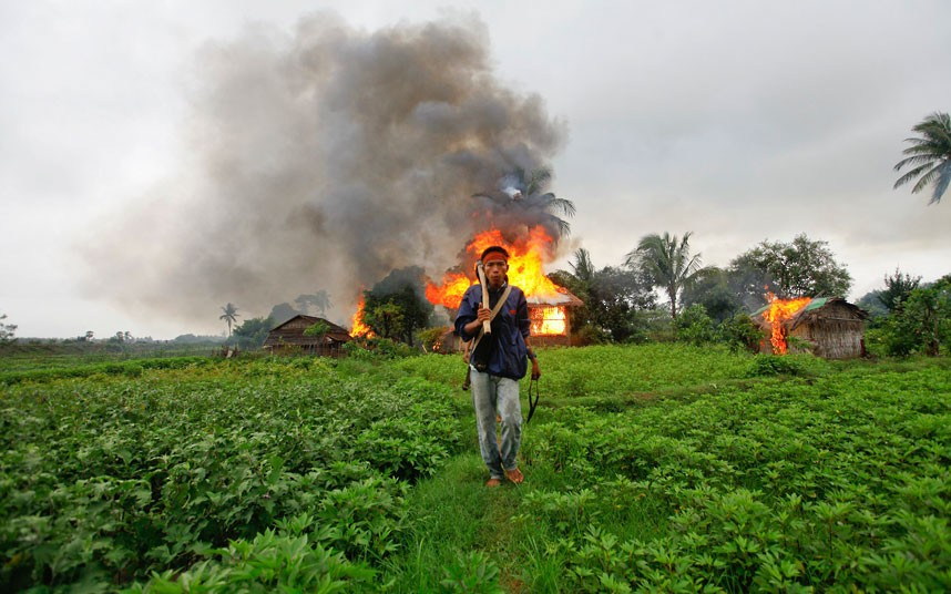 A Rakhine man as he walks in front of houses that were burnt during fighting between Buddhist Rakhine and Muslim Rohingya communities in Sittwe Picture: REUTERS